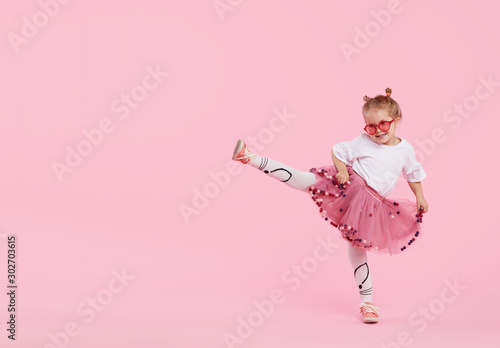 Happy childhood. Funny child girl in tulle skirt jumping and having fun isolated on pink background. Celebrating a vibrant carnival for kids, birthday party. True emotions. Space for text