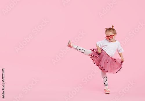 Szczęśliwe dzieciństwo. Śmieszna dziecko dziewczyna w tiulowej spódnicie skacze zabawę odizolowywającą na różowym tle i ma. Świętujemy żywy karnawał dla dzieci, przyjęcie urodzinowe. Prawdziwe emocje. Miejsce na tekst