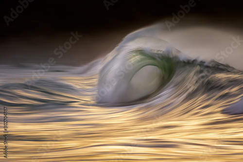 Photo of a big wave breaking at sunset with in camera panning technique - 302704887