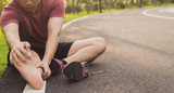 Young man massaging his painful foot from jogging and running on running track. Sport and exercise concept.
