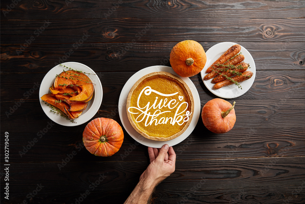 Fototapeta partial view of male hand near plate with pumpkin pie and give thanks illustration, baked whole carrot, sliced and whole pumpkins on dark wooden table