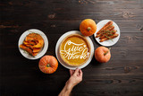 partial view of male hand near plate with pumpkin pie and give thanks illustration, baked whole carrot, sliced and whole pumpkins on dark wooden table