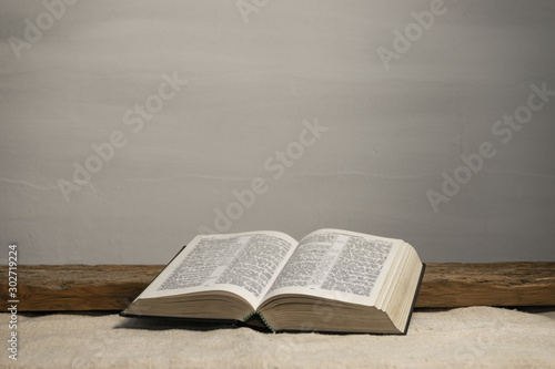 Photo  Open Holy Bible on a old wooden table and white wall background