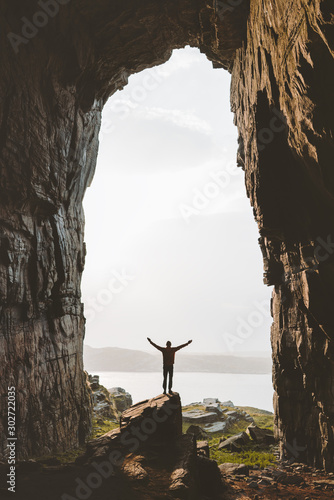 Obraz Man standing alone in cave Travel adventure vacations happy raised hands tourist success wellness concept Kirkehelleren grotto in Norway - fototapety do salonu