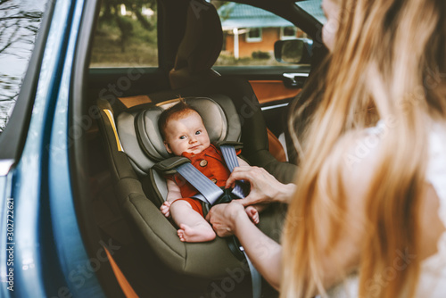 Mother putting baby in safety car seat family lifestyle child care transportatio Fototapet