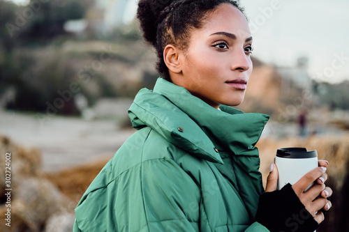 Pinturas sobre lienzo  Side view of beautiful African American girl in down jacket with cup to go dream