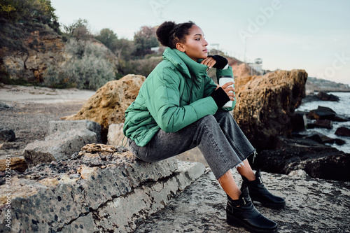 Cuadros en Lienzo  Side view of beautiful casual African American girl in down jacket with cup to g
