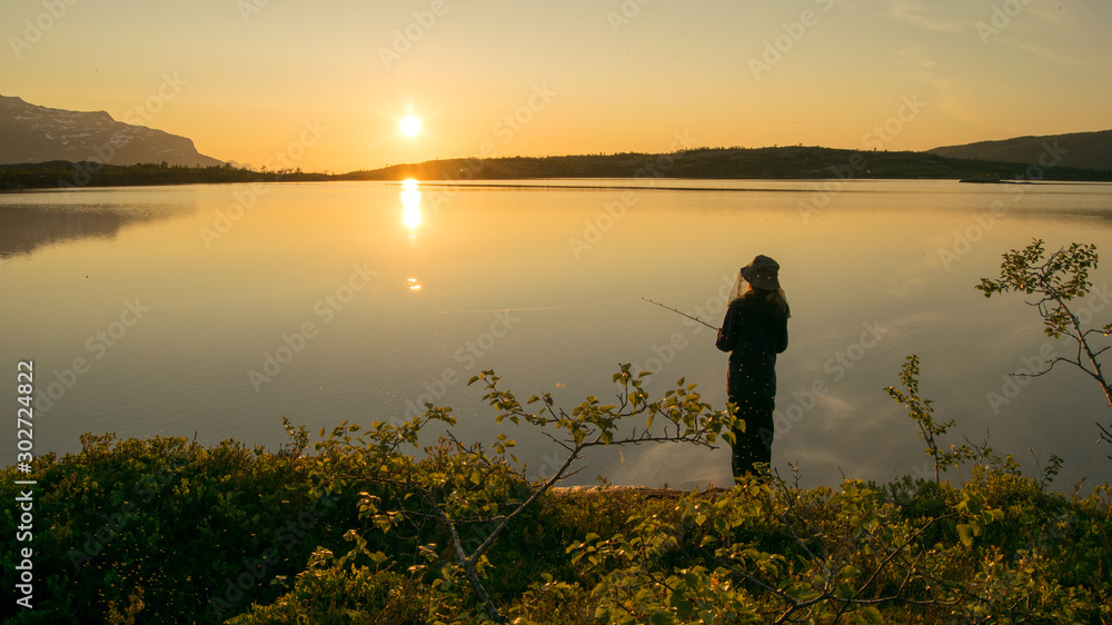 Fototapety, obrazy: Midnightsun in Scandinavia. A girl is fishing in front of the great scenery. A mosquito hat is a necessity.