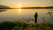 Midnightsun in Scandinavia. A girl is fishing in front of the great scenery. A mosquito hat is a necessity.