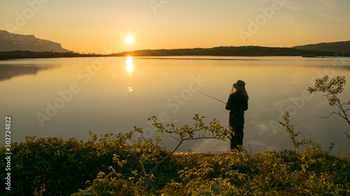 Poster Natuur Midnightsun in Scandinavia. A girl is fishing in front of the great scenery. A mosquito hat is a necessity.