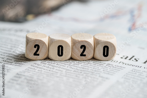Obraz cubes with number 2020 on a newspaper - fototapety do salonu
