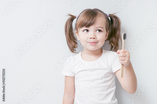 Stampa su Tela child girl brushes her teeth with a bamboo toothbrush