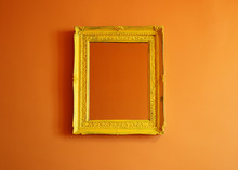 Yellow Antique Empty Photo Frame Isolated On Orange Colored Wall