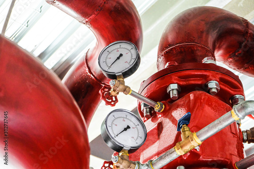 Pressure gauges on a red tubes. Industrial fire extinguishing system manometers.