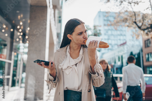 girl with a tablet pc in hands is walking along a city street against the backgr Canvas Print