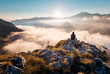 Leinwanddruck Bild - Man sitting an top of mountain at sunrise and enjoying the view