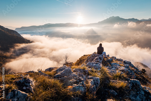Man sitting an top of mountain at sunrise and enjoying the view - 302741008