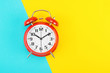 canvas print picture - Red retro alarm clock with a big dial, on divided diagonally blue-yellow background. The concept of time, delay, morning rise, the appointed meeting. Layout with copy space for your text. Flat lay.