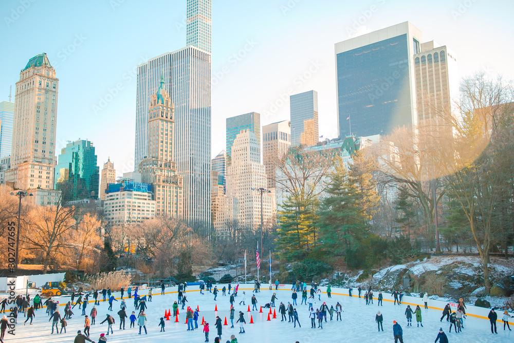 Fototapeta Ice skaters having fun in New York Central Park in winter