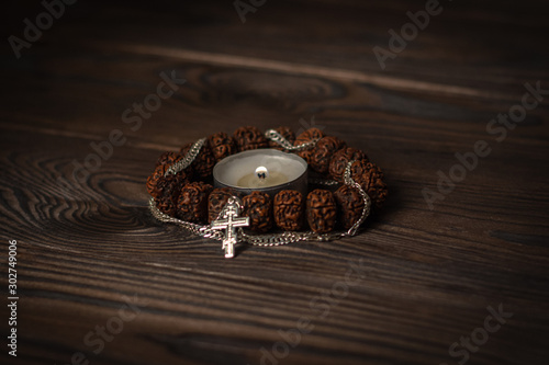 composition symbols of faith, focus on a burning candle, around it a Buddhist wooden bracelet intertwined with a Christian cross on a chain Wallpaper Mural