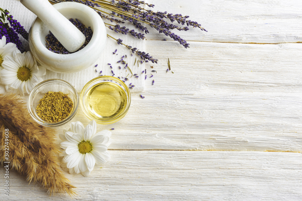 Fototapeta Composition with dried lavender flowers in white marble pestle and mortar and natural chamomile oil cosmetic in glass jar on white background, top view with free copy space