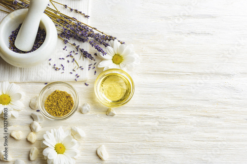 Spoed Fotobehang Lavendel Composition with dried lavender flowers in white marble pestle and mortar and natural chamomile oil cosmetic in glass jar on white background, top view with free copy space