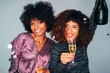 canvas print picture - Portrait of Happy Two Young Beautiful African American friends toasting the champagne glasses with each other. Celebrating a Christmas holidays.