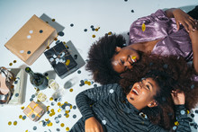 Top View Of Two Happy American African Women Laying On The Floor Celebrating New Years Eve With Confetti, Gift And Champagne.