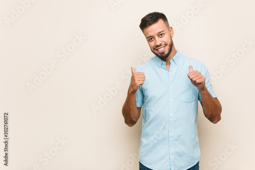 Fototapeta  Young south-asian man raising both thumbs up, smiling and confident