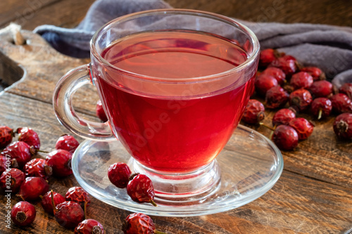 A cup of herbal tea with dried rose hips on a table Wallpaper Mural
