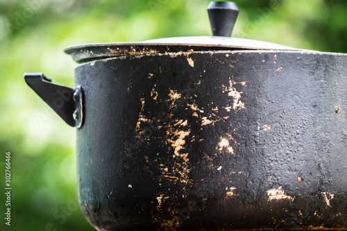 A dirty old metal pot. Close-up photo. Fototapeta