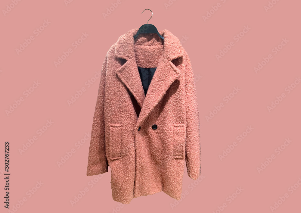 Fototapeta Fashionable Pink women Faux shearling coat on a hanger isolated on pink background.  Composition of clothes. Flat lay, top view, copy space. Winter clothes pattern. Ladies' Trench Coat. Pattern