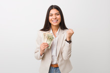 Young Arab Business Woman Holding Dollars Cheering Carefree And Excited. Victory Concept.