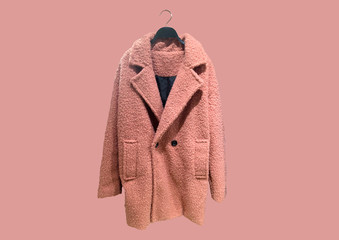 Fashionable Pink women Faux shearling coat on a hanger isolated on pink background.  Composition of clothes. Flat lay, top view, copy space. Winter clothes pattern. Ladies' Trench Coat. Pattern