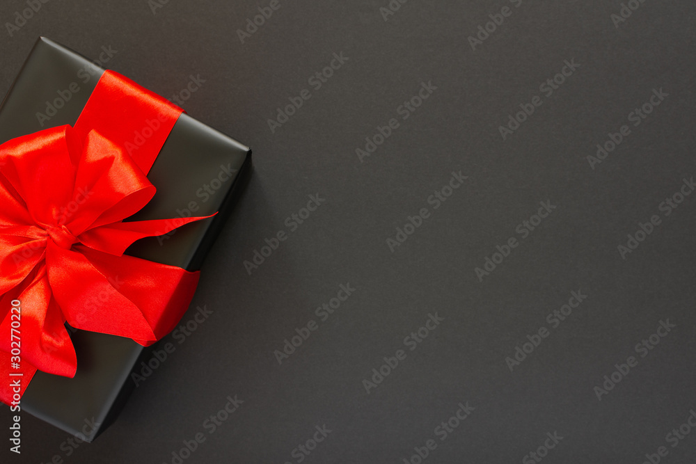 Fototapety, obrazy: Festive background with gift, black gift box with red ribbon and bow on black background, black friday concept, flat lay, top view