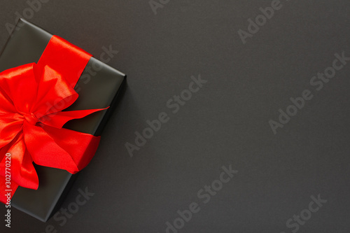 Photo  Festive background with gift, black gift box with red ribbon and bow on black ba