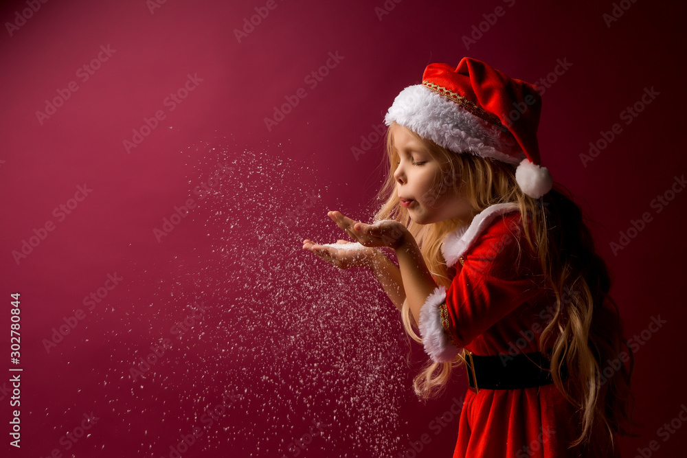 Fototapeta little blonde girl in a Santa suit blows snow off her hands. red background isolate. space for text