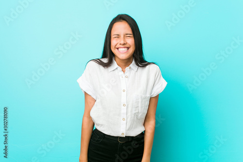 Young hispanic cool woman against a blue wall laughs and closes eyes, feels relaxed and happy Canvas