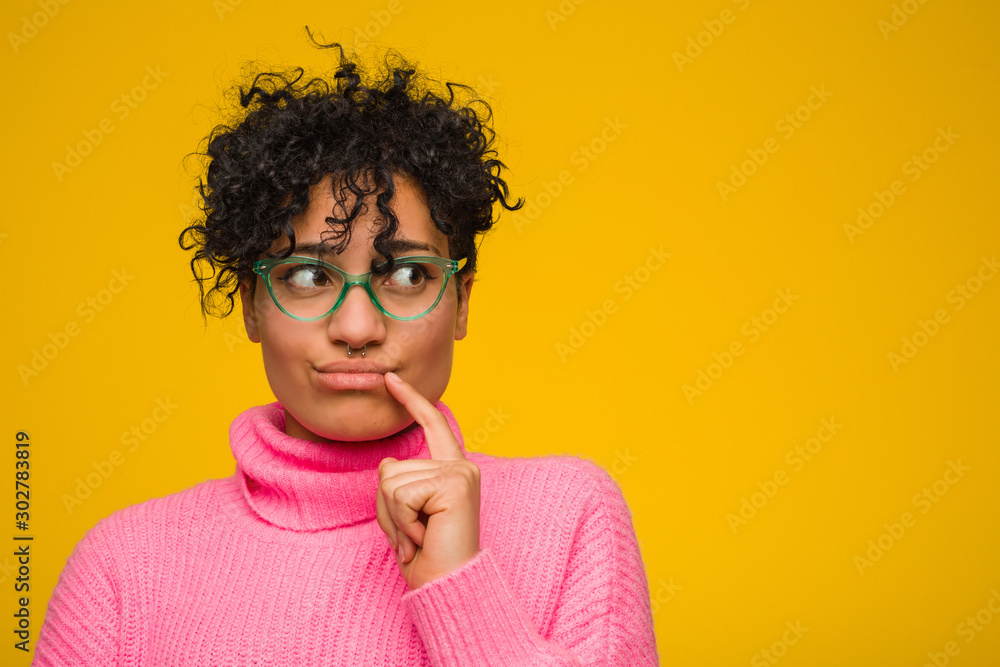 Fototapeta Young african american woman wearing a pink sweater looking sideways with doubtful and skeptical expression.