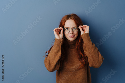 Fotomural Pretty woman with hands raised to her glasses