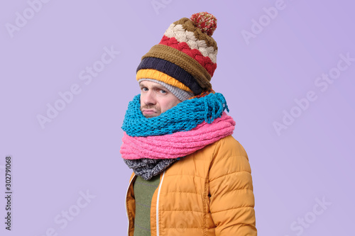 фотография Handsome caucasian funny man in several hats and scarfs.