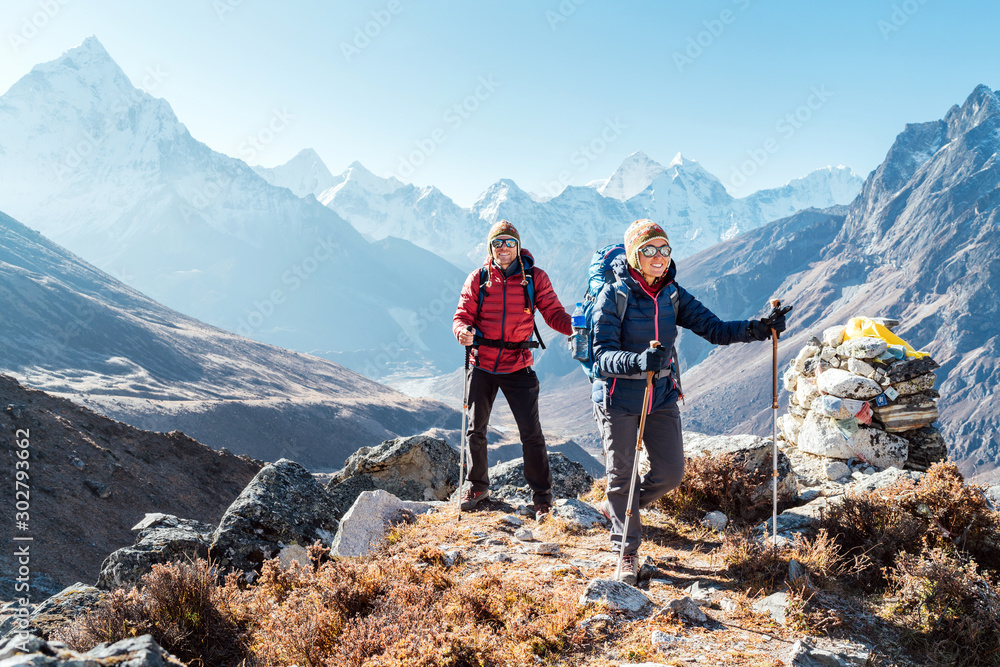 Fototapeta Couple following Everest Base Camp trekking route near Dughla 4620m. Backpackers carrying Backpacks and using trekking poles and enjoying valley view with Ama Dablam 6812m peak