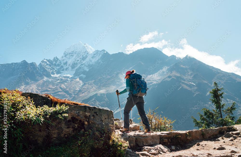 Fototapety, obrazy: Young hiker backpacker woman using trekking poles enjoying Everest Base Camp trekking route with Thamserku 6608m mountain on background during high altitude Acclimatization walk in Sagarmatha NP,Nepal