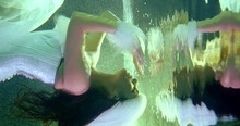 Brunette With Long Hair Dressed In A White Dress With White Fur And A White Fur Hat. It Slowly Approaches The Surface Of The Water And Passes Through It. Reflection On The Water Surface. Green Light