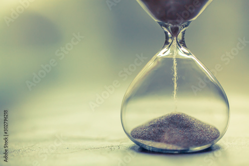 Sand running through the bulbs of an hourglass measuring the passing time in a countdown to a deadline, on a bright background with copy space Wallpaper Mural