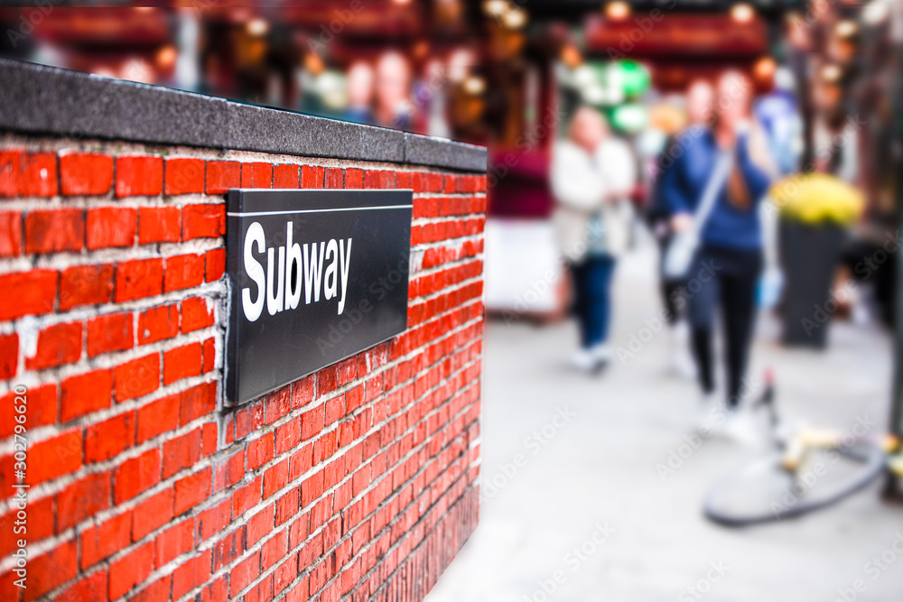Fototapety, obrazy: New York City street corner subway entrance with sign on brick wall and blur of women walking in the background