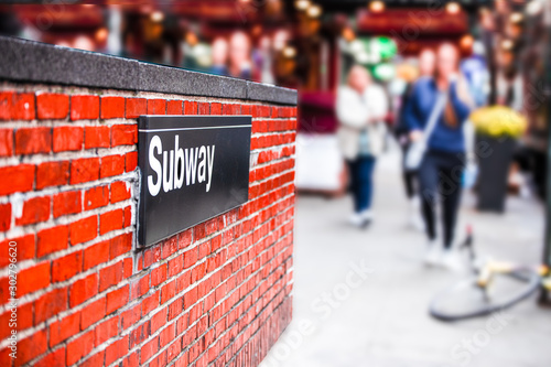 New York City street corner subway entrance with sign on brick wall and blur of women walking in the background