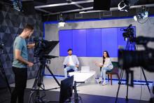 Presenters And Video Camera Operator Working In Studio. News Broadcasting