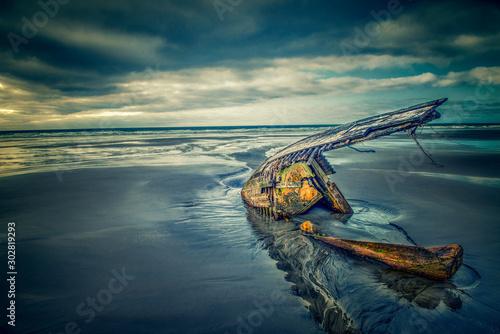 Fotografija Shipwrecked boat on the sandy beach