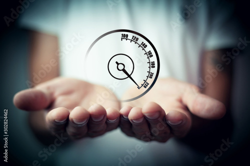 Photo man holding a speedometer icon in his hands a sharp acceleration of speed